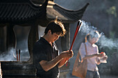 Man praying with incense sticks, Puji Si Temple, Buddhist Island of Putuo Shan near Shanghai, Zhejiang Province, East China Sea, China