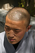 Shaolin monk with symbolic burn marks on his shaven head, Shaolin Monastery, known for Shaolin boxing, Taoist Buddhist mountain, Song Shan, Henan province, China