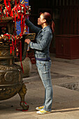 young modern woman, money and red ribbons are donated for long life, health and wealth, Temple, Tai Shan, Shandong province, Taishan, Mount Tai, World Heritage, UNESCO, China, Asia