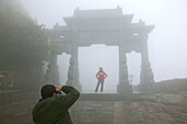 pilgrims, tourists in rain capes, entrance Bixia Si temple in fog, Tai Shan, Shandong province, Taishan, Mount Tai, World Heritage, UNESCO, China, Asia