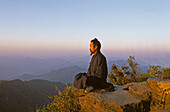 monk meditating in lotus position, sunrise, Golden Hall, Jindian Gong, peak 1613 metres high, Wudang Shan, Taoist mountain, Hubei province, Wudangshan, Mount Wudang, UNESCO world cultural heritage site, birthplace of Tai chi, China, Asia