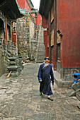Elderly taoist monk in an alleyway in the village Wudang Shan, Taoist mountain, Hubei province, Mount Wudang, UNESCO world cultural heritage site, birthplace of Tai chi, China