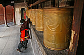 Child monk turning the prayer wheels at the base of the Great White Pagoda during the birthday celebrations for Wenshu, Tayuan Monastery, Wutai Shan, Five Terrace Mountain, Buddhist Centre, town of Taihuai, Shanxi province, China