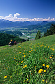 Hiker sitting on a bench at Kranzhorn with a view over the Inn valley, Kaiser Mountain Range and Central Eastern Alps, Chiemgau Alps, Tyrol, Austria
