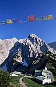 Stripsenjoch alm with Totenkirchl and Buddhist prayer flags, Stripsenjochhaus, Kaiser mountain range, Tyrol, Austria