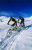Zwei Mountainbiker fahren durch tiefen Schnee, Serfaus, Tirol, Österreich