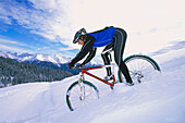 Man riding a mountain bike downhill in the snow, Serfaus, Tyrol, Austria