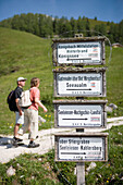 Two hikers and sign post at the Jenner Mountain, near Lake Koenigssee, near Berchtesgaden, Berchtesgadener Land, Bavaria, Germany