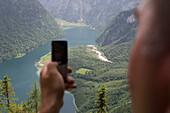 Man photographing Lake Koenigssee using his Mobile Phone, Near Watzmann Mountain, Berchtesgaden, Berchtesgadener Land, Bavaria, Germany