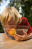 Boy eating an apple in a dish with water, children's birthday party
