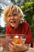 Boy bending over a dish with water and an apple, children's birthday party