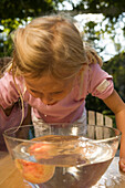 Girl bending over a dish with water and an apple, children's birthday party