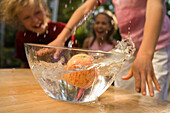 Water swashing out of a dish with an apple, children in background, children's birthday party