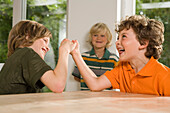 Two boys arm wrestling, one boy standing in background, children's birthday party