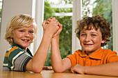 Two boys arm wrestling, children's birthday party