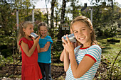 Four girls playing with a tin can phone, children's birthday party