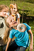 Children playing donut catching, children's birthday party