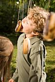 Boy playing donut catching, children's birthday party