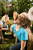 Girls playing donut catching, children's birthday party