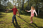 A girl and a boy playing egg-and-spoon race, children's birthday party