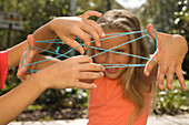 Two girls playing cat's cradle, children's birthday party