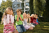 Children crouching side by side on grass and covering eyes by hands, children's birthday party