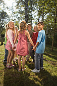 Group of children holding hands in circle, children's birthday party