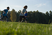 Two boys running over field, children's birthday party