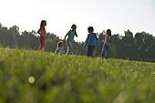Children running over field, children's birthday party