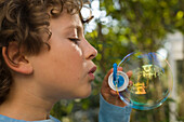 Boy blowing soap bubbles, children's birthday party