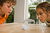 Girl and boy playing Cotton Wool Blowing, children's birthday party