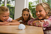 Three girls playing Blowing Cotton Wool, children's birthday party