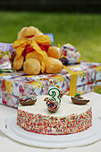 Birthday cake and presents on table