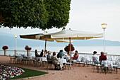 Tourists sitting in an cafe at Lake Grada, Italia