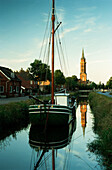 Sailing ship on canal, church in background, Westrhauderfehn, Rhauderfehn, East Friesland, Lower Saxony, Germany