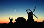 Twin windmills in sunset with moon, Greetsiel, East Friesland, Lower Saxony, Germany