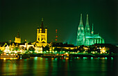 View over River Rhine to illuminated city hall, Great St. Martin Church and Cologne Cathedral at night, Cologne, North Rhine-Westphalia, Germany