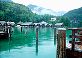 View of Koenigssee with wooden houses and mountains in background, Berchtesgaden National Park, Schoenau, Bavaria, Germany