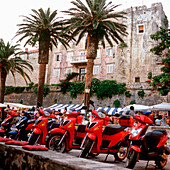 Red scooter parking in a row near a market, old stone building in background, Korcula, Dalmatia, Croatia