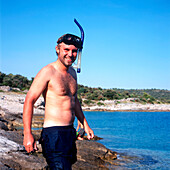 Man with diving goggles at Adriatic Seashore, Dalmatia, Croatia