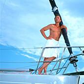 Man with towel around waist, leaning against sailboat's mast, Adriatic Sea, Dalmatia, Croatia