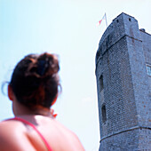 Woman looking at defense tower of the mediaeval city wall, Dubrovnik, Dalmatia, Croatia