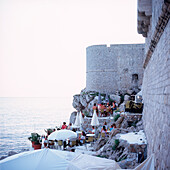 Tourists sitting in the buza bar at city wall, Dubrovnik, Dalmatia, Croatia