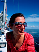 Woman wearing sunglasses on a sailboat, Bay of Kiel between Germany and Denmark