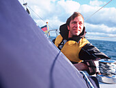 Man wearing lifejacket on sailboat, Bay of Kiel between Germany and Denmark