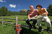 A couple reading map sitting on a fence, Gowilalm, Austria