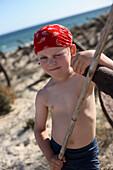 Boy playing pirate at a rosty anchor on beach, Ilha de Tavira, Tavira, Algarve, Portugal