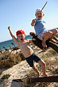 Two boys playing pirates on a rusty anchor at beach, Ilha de Tavira, Tavira, Algarve, Portugal