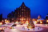 A big house, building and a christmas tree in the winter. Evening, Banff Fairmont Springs Hotel, Rocky Mountains, Alberta, Canada, North Amerika