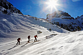 Three people on a ski tour to the top of Maljovica, Wind is blowing the snow around, Rila Mountains, Bulgaria, Europe